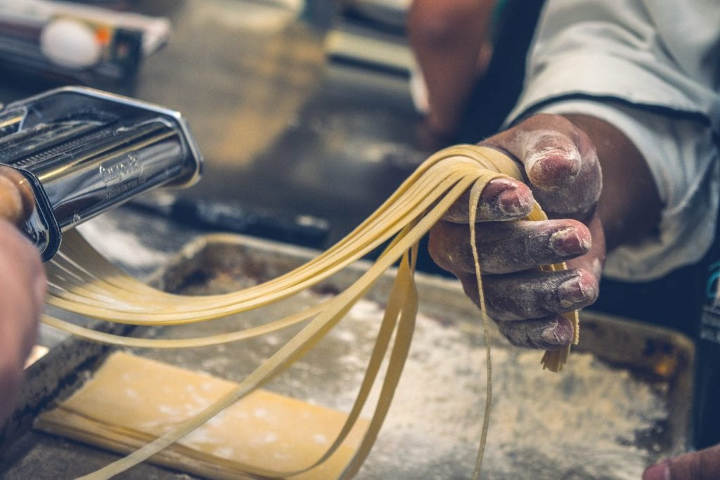 A chef in a white coat making fresh pasta by hand